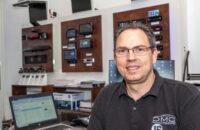 Andy Ehrenhuber SAM Technixx vor der Demowand mit Testgeräten